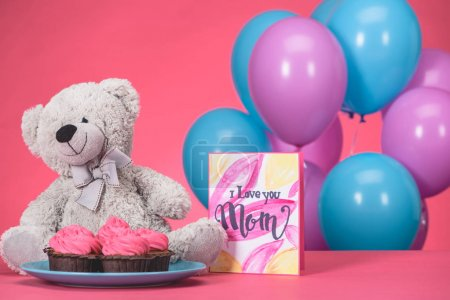 teddy bear with cupcakes and postcard with text I Love You Mom, mothers day concept