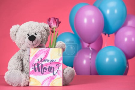 teddy bear with pink tulip and postcard with text I Love You Mom, mothers day concept