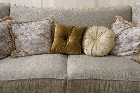 Velvet pillows on grey sofa in room