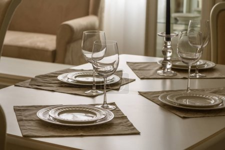 Set of dinner tableware on table in dining room
