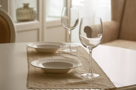 Wineglasses and white plates on table in dining room