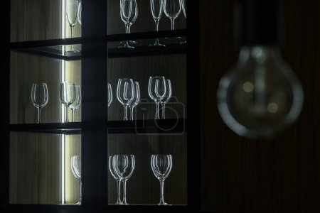 Empty clean glasses organized in wooden cupboard
