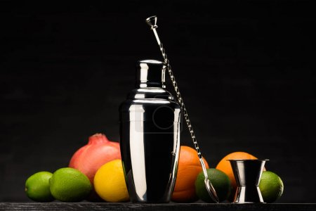 shaker for preparing alcohol cocktail and fruits on table isolated on black