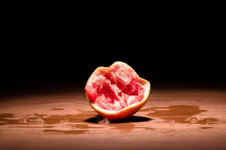 squeezed grapefruit on wooden table in dark room