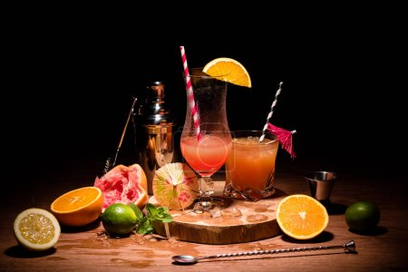 tasty alcohol cocktails on wooden board with fruits on table