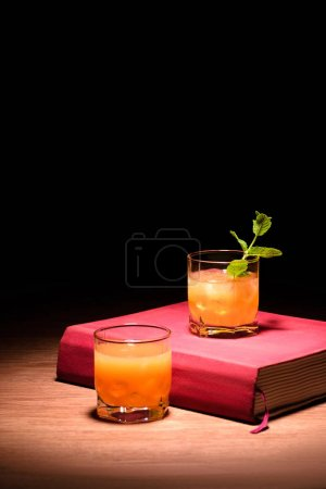 orange alcohol cocktails with mint on pink book on table