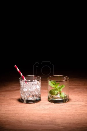 two glasses with ice cubes and mint for alcohol drinks on table