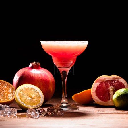 Photo pour Boire de l'alcool rouge avec des fruits mûrs sur table en bois - image libre de droit