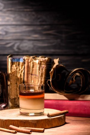 alcohol drink on wooden board with cinnamon sticks on table