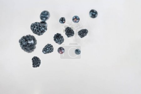 Juicy berries dropping into milk on white background