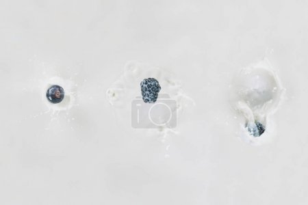 Three berries in row falling into milk on white background