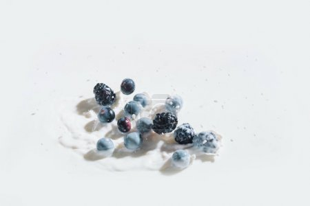 Juicy berries falling in milk with drops on white background