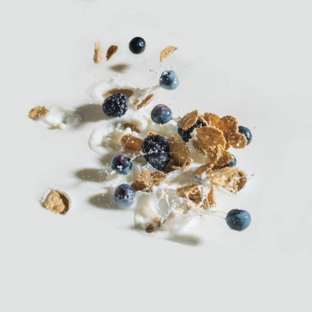 Cereals and berries splashing into milk on white background