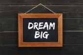 blackboard with dream big inscription hanging on wooden wall