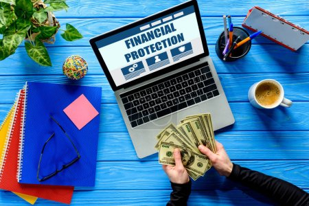 Business person counting dollars by laptop on blue wooden table with stationery, Financial protection lettering