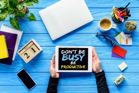 hands holding tablet on blue wooden table with money and stationery, Dont be busy be productive lettering