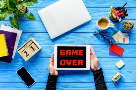 hands holding tablet on blue wooden table with money and stationery, Game over lettering