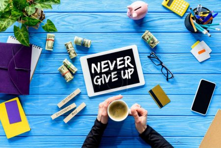 Hands holding coffee cup on blue wooden table by money and digital tablet, Never give up inspiration