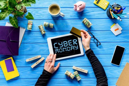 Hands holding tablet and credit card on blue wooden table with money, Cyber monday lettering
