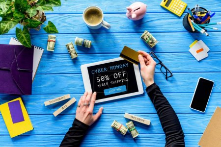 Hands holding tablet and credit card on blue wooden table with money, Cyber monday, free shipping lettering