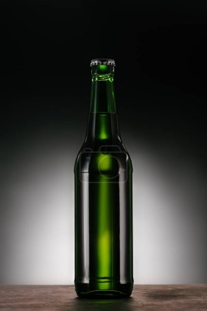 close up view of bottle of beer on dark grey backdrop