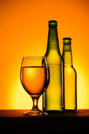 close up view of bottles and glass of beer on surface on orange background