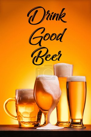 close up view of arranged mugs of cold beer with froth and drink good beer inscription on orange background