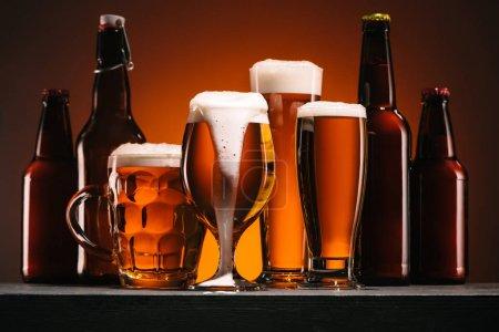 Photo pour Bouchent vue de bouteilles et de chopes de bière sur fond orange - image libre de droit