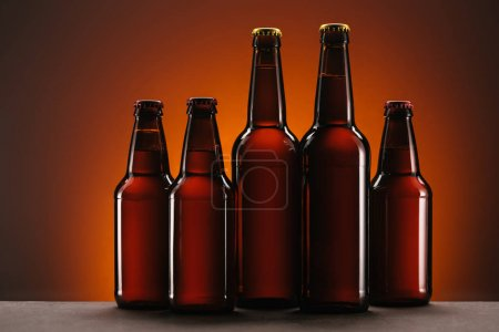 Photo for Close up view of arranged bottles of beer on orange backdrop - Royalty Free Image