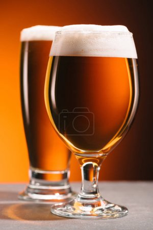 selective focus of arrangement of glasses of beer with froth on orange backdrop