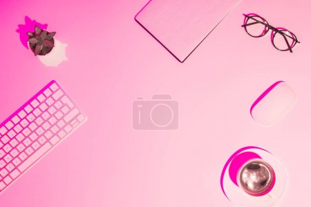 pink toned picture of coffee cup, plant, eyeglasses, empty textbook, computer keyboard and mouse on table