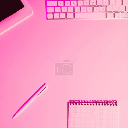 pink toned picture of digital tablet, pen, textbook and computer keyboard on table