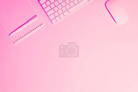 pink toned picture of pen, textbook, computer keyboard and mouse on table