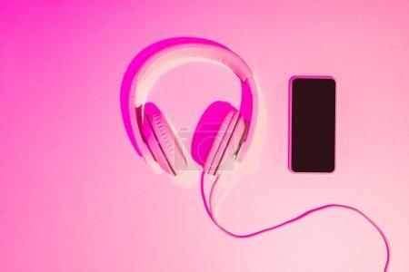 Photo pour Image rose tonique de smartphone avec écouteurs sur fond rose - image libre de droit