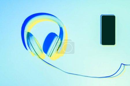Photo pour Bleu photo tonique du smartphone avec un casque sur fond bleu - image libre de droit