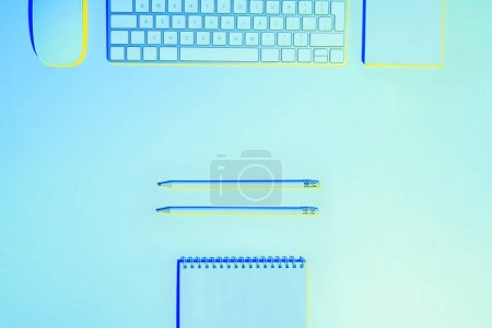 blue toned picture  of computer keyboard and mouse, pencils and empty textbook