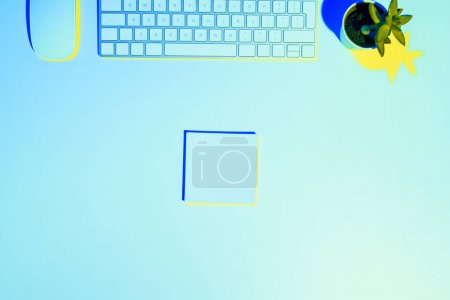 blue toned picture of computer keyboard and mouse, plant ant sticky note