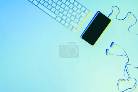 blue toned picture of smartphone, earphones and computer keyboard