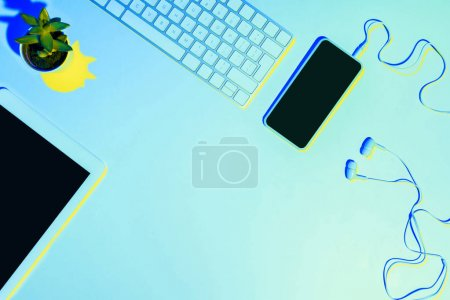 blue toned picture of smartphone, earphones, computer keyboard, plant and digital tablet