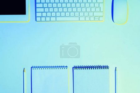 blue toned picture of empty textbooks, pencils, digital tablet, computer mouse and keyboard