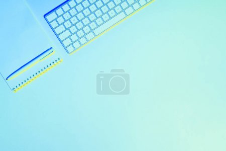 blue toned picture of computer keyboard, empty textbook and pen