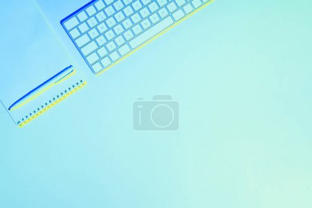 Photo for Blue toned picture of computer keyboard, empty textbook and pen - Royalty Free Image