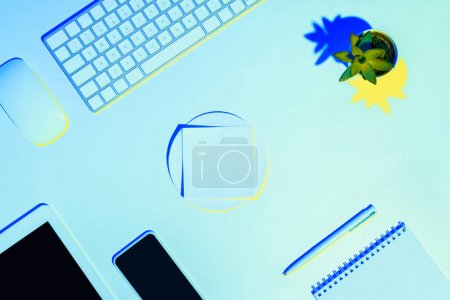 blue toned picture of digital tablet, smartphone, computer keyboard and mouse, plant, textbook, pen and sticky note