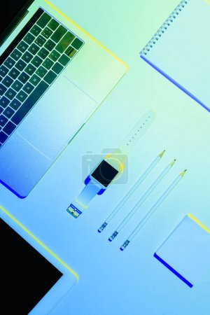 blue toned picture of laptop, digital tablet, smartwatch, pencils, textbook and sticky note