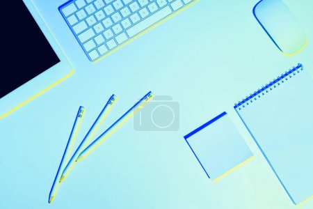 blue toned picture of pencils, digital tablet, computer keyboard and mouse, textbook and sticky note