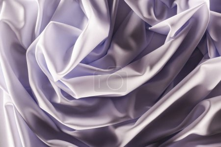 full frame of folded elegant purple silk fabric as background