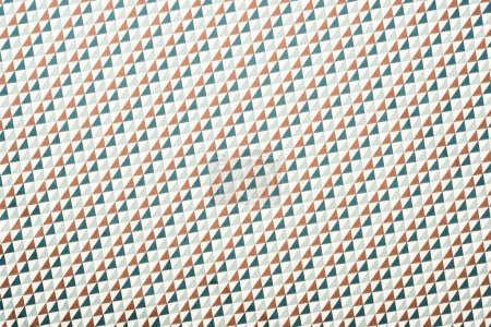 full frame of white fabric with green and brown triangles ornament background