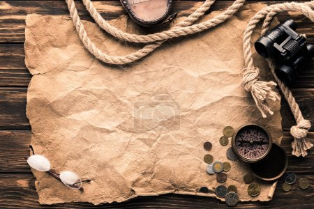 top view of blank crumpled paper with compass, binoculars and rope on rustic wooden surface