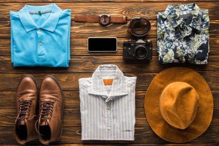Photo pour Vue de dessus des vêtements élégants avec appareil photo argentique et smartphone sur la surface en bois, concept de voyage - image libre de droit
