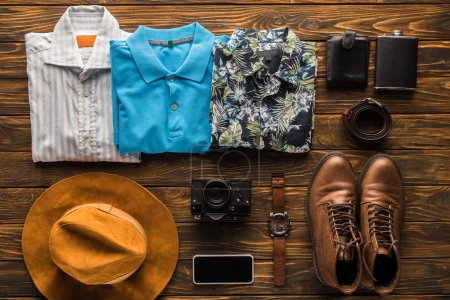 top view of stylish traveller stuff kit on rustic wooden tabletop